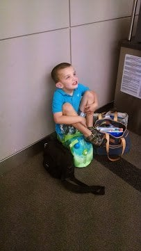 Kevin sitting on his Trunki carry on in the Denver airport.