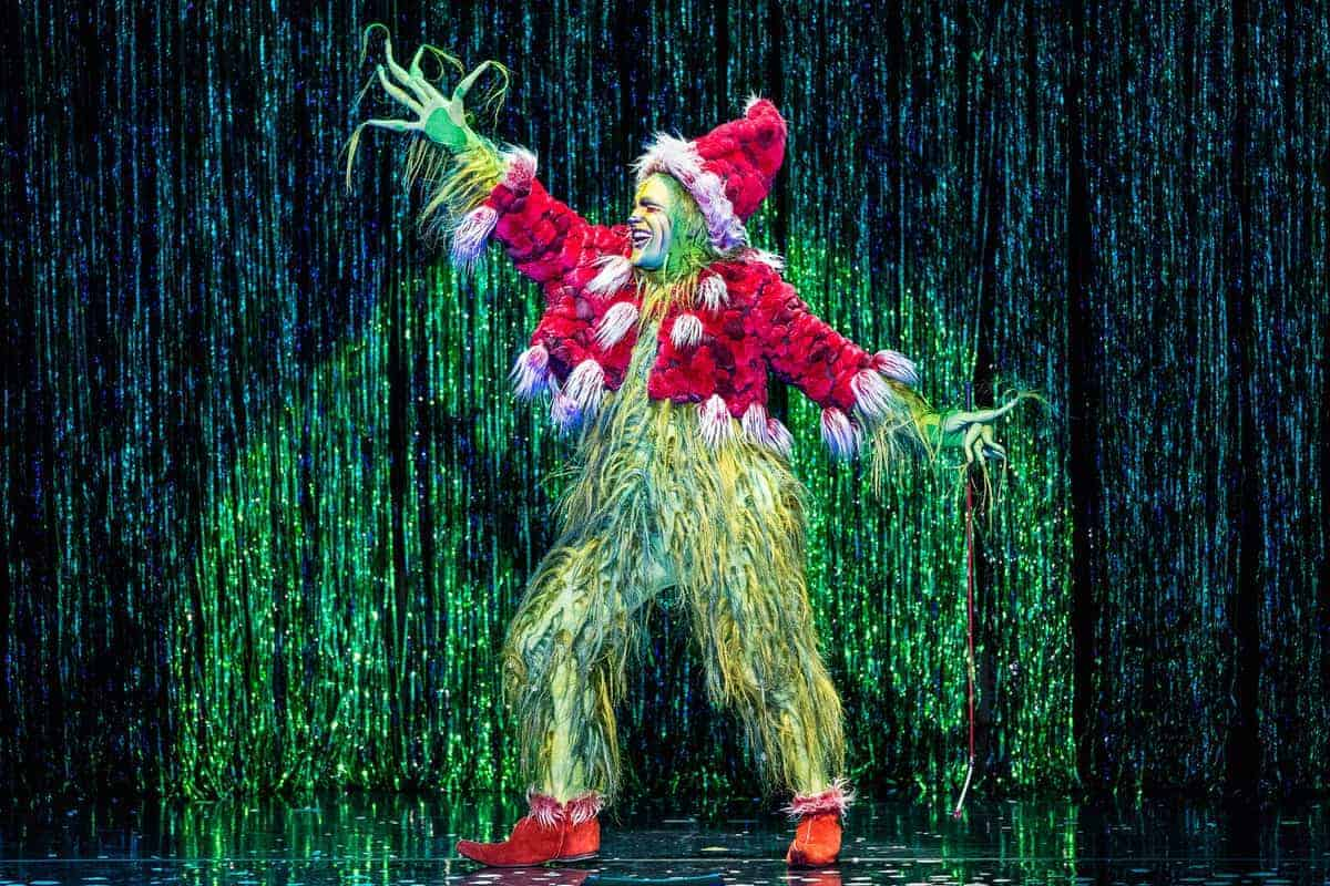 Dr Seuss' How the Grinch Stole Christmas! the Musical The grinch smiling and laughing and dancing