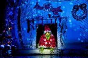 Dr Seuss' How the Grinch Stole Christmas! the Musical the grinch sitting in a fireplace