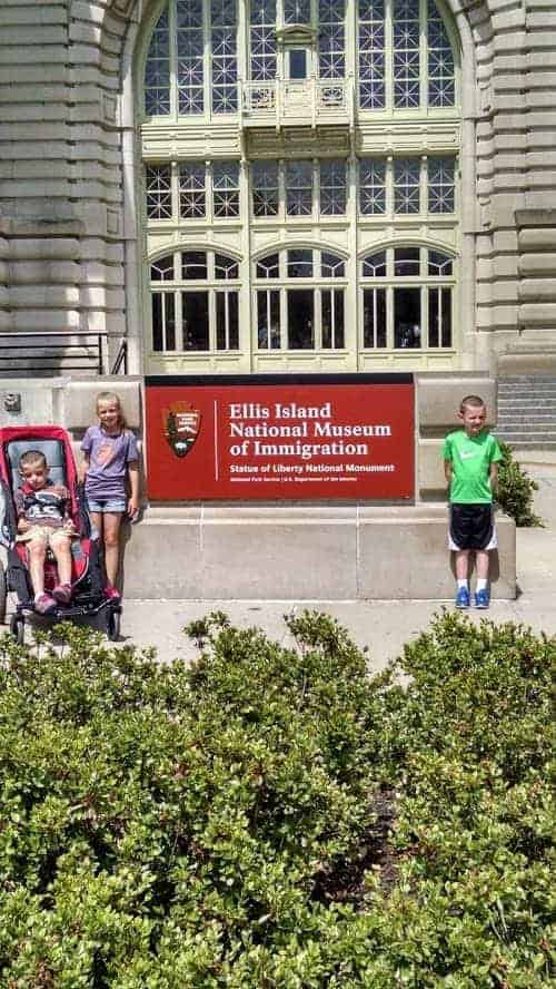 kids standing in front of ellis island nyc